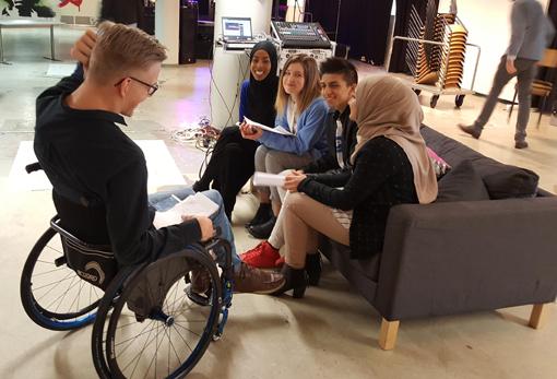 pyörätuolissa istuva nuori mies haastattelee neljää nuorta, jotka istuvat sohvalla, kaikki hymyilevät