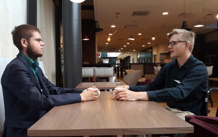 Matias ja Marcus istuvat pöydän molemmin puolin ja katsovat toisiaan
